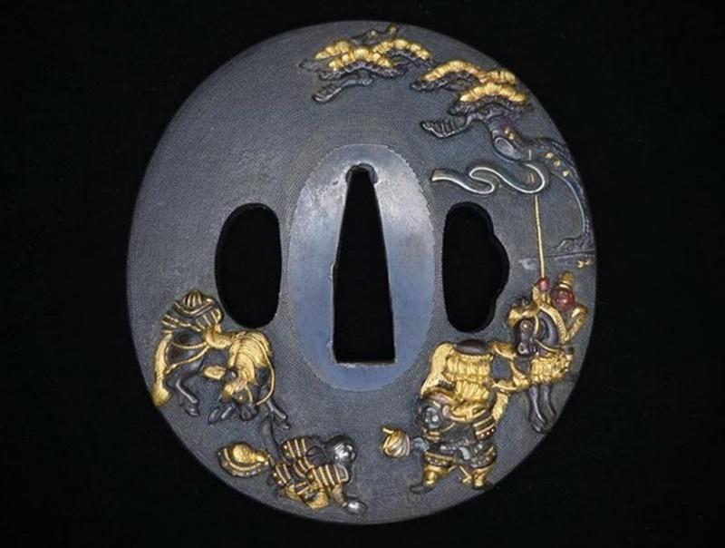 【刀装具・鍔】後藤光邦 高盛彫合戦図赤銅魚子地鍔を買取致しました。